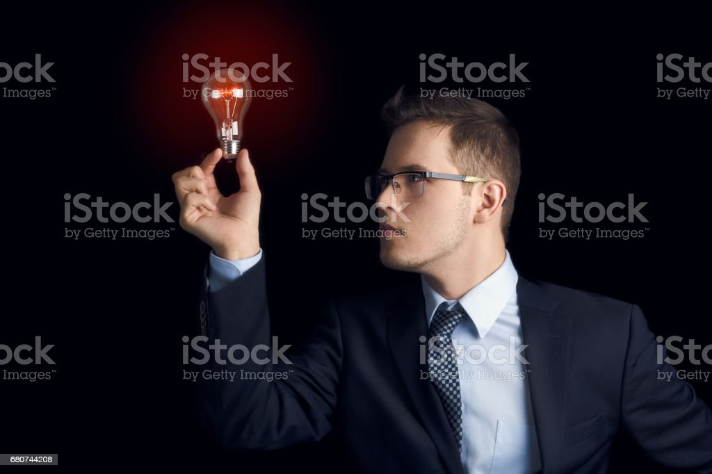 A man in a business suit looks at the burning light bulb he holds between his fingers as a symbol of knowledge and ideas, on a black background. stock photo