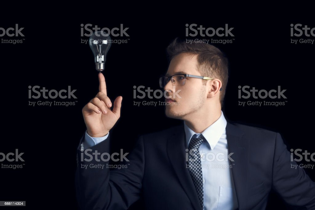 A man in a business suit looks at the light bulb he holds between his fingers as a symbol of knowledge and ideas, on a black background. stock photo