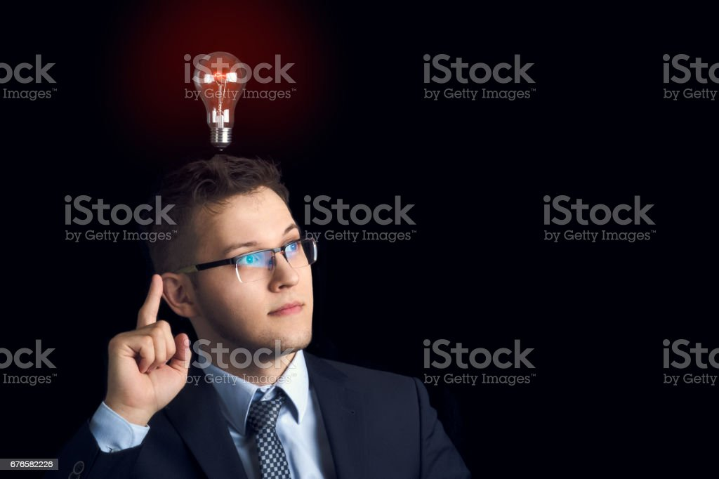 A man in a business suit on a black background with a lighted bulb over his head came up with a good idea. stock photo