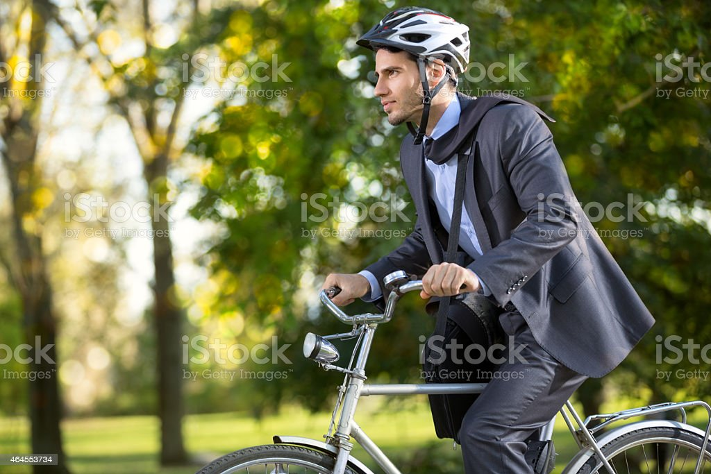 man in a business suit on  bicycle stock photo