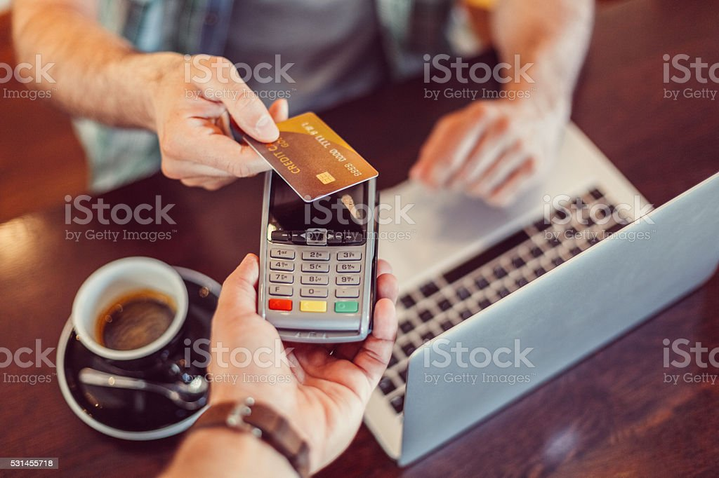 Man in a cafe making contactless credit card payment stock photo