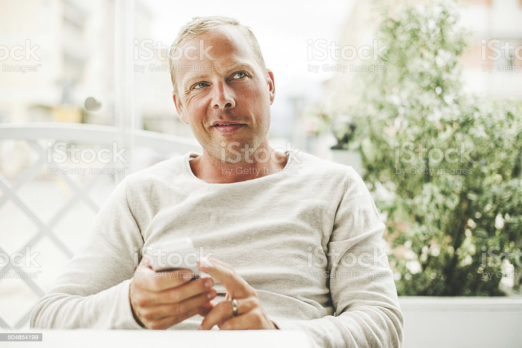 Man in a cafe using his smart phone royalty-free stock photo