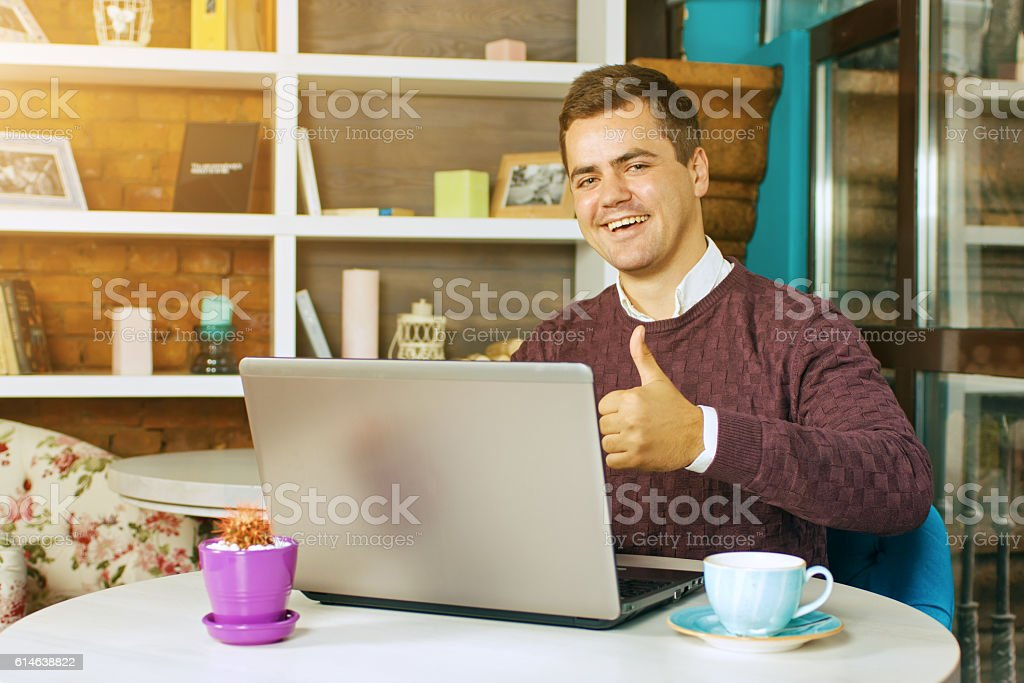 Man in a cafe with laptop smiling stock photo