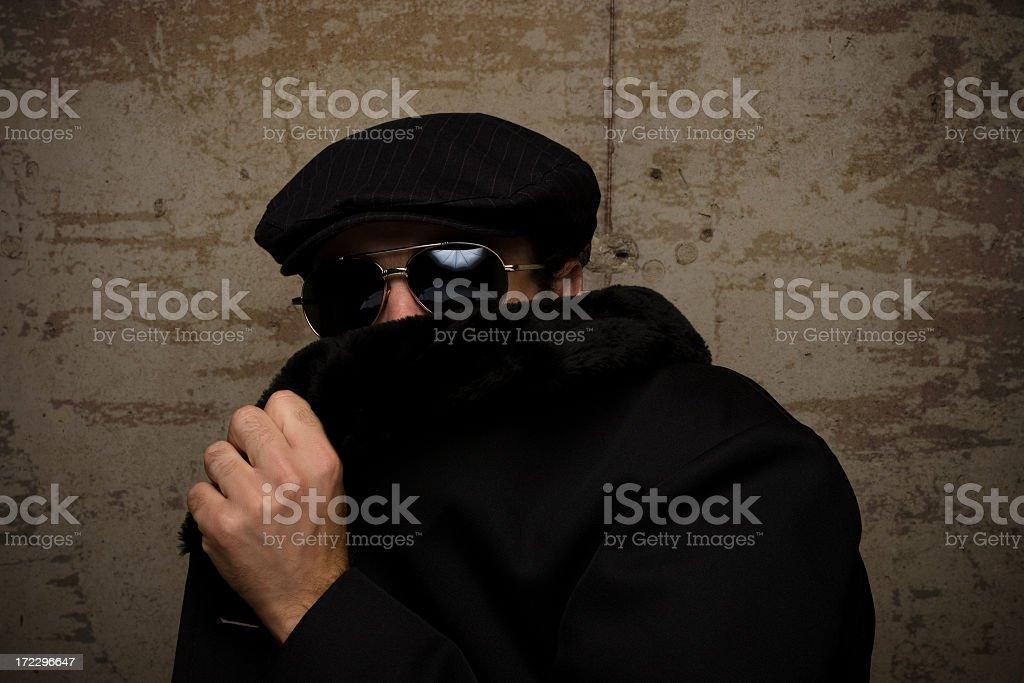 A man in a cap and dark glasses hides his face with his coat royalty-free stock photo