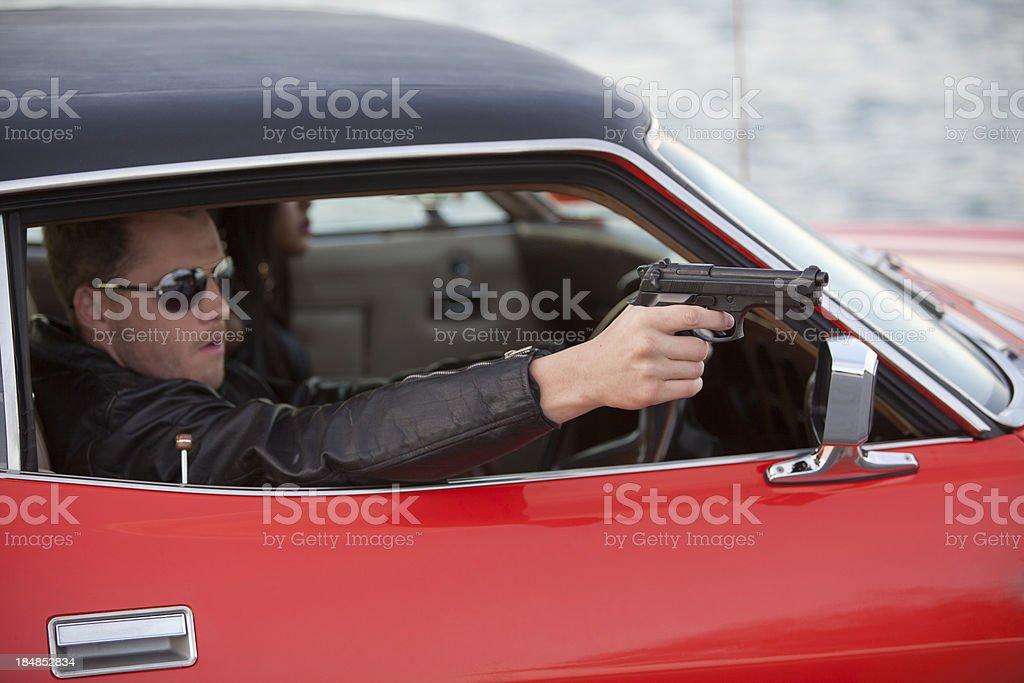 Man In a Car Pointing Gun royalty-free stock photo