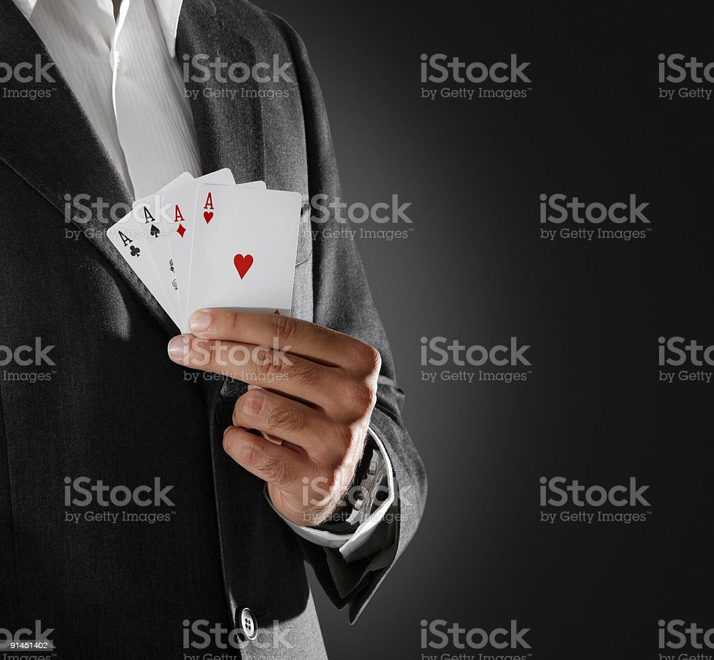 Man in a dark jacket holding playing cards with four aces stock photo
