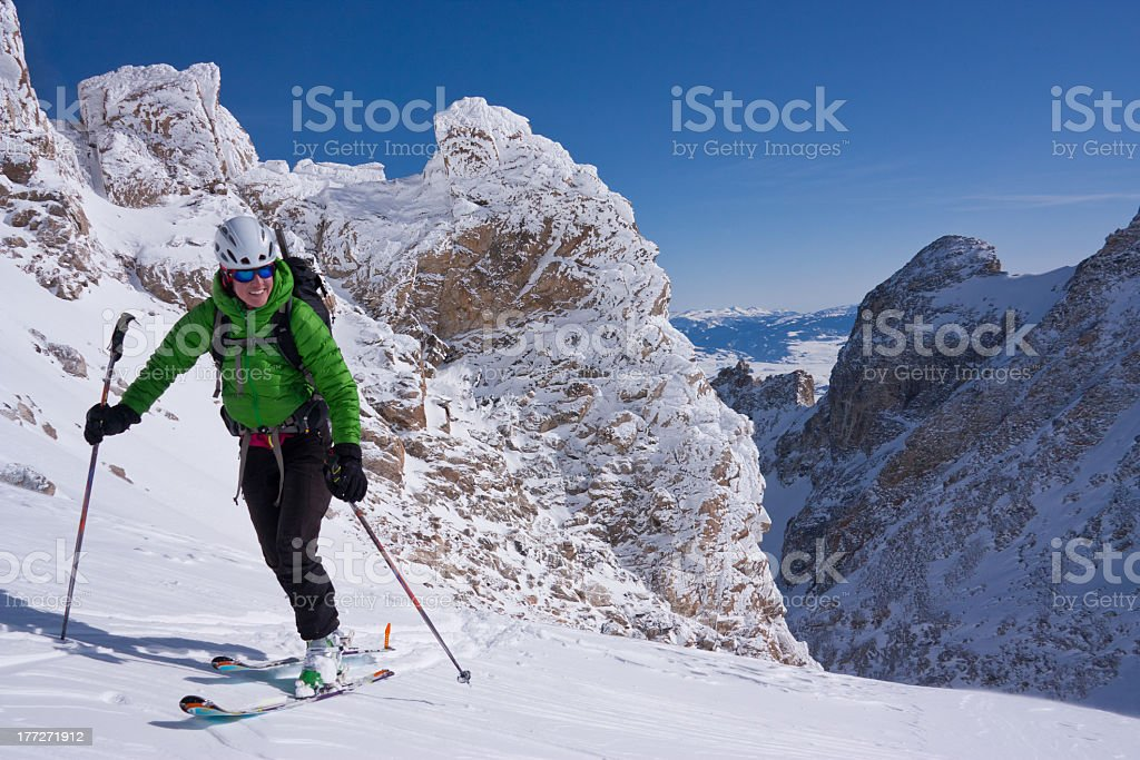 A man in a green coat skiing in Wyoming stock photo