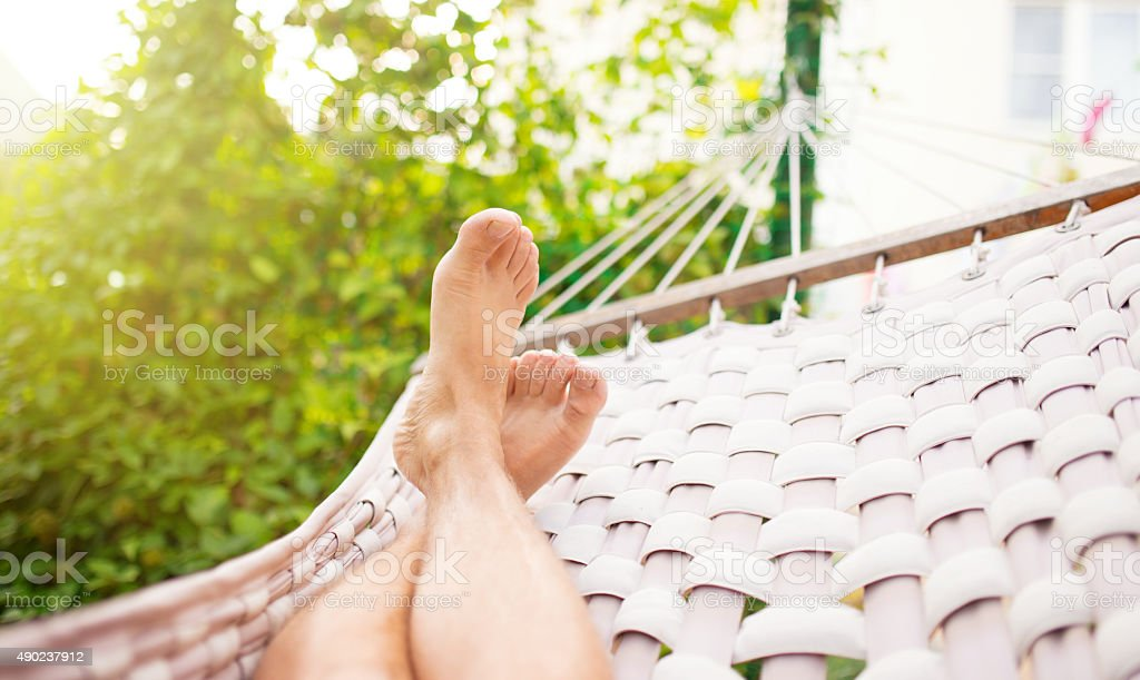 Man in a hammock on a summer day stock photo