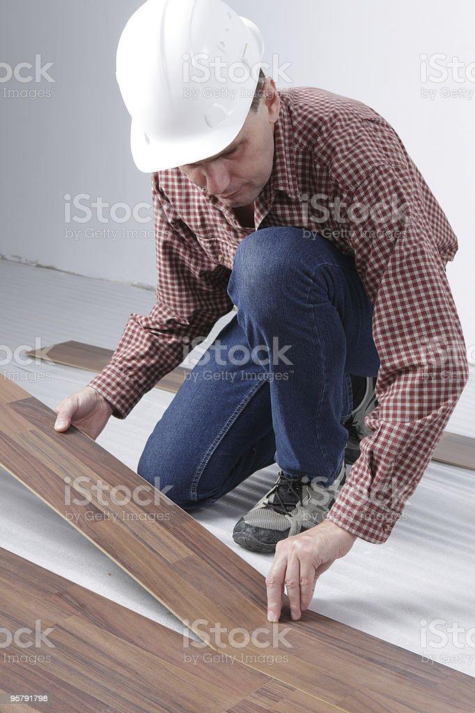 Man in a hard hat installing laminate flooring royalty-free stock photo