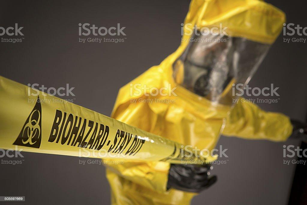 Man in a hazmat Suit holding biohazard warning tape stock photo