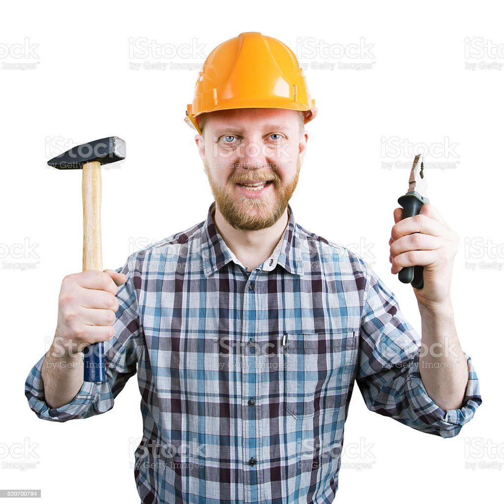 Man in a helmet with a hammer and pliers stock photo