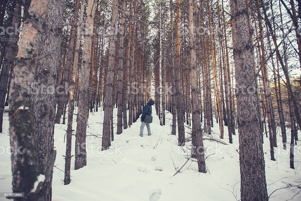 Man in a hood looking at forest plantations stock photo