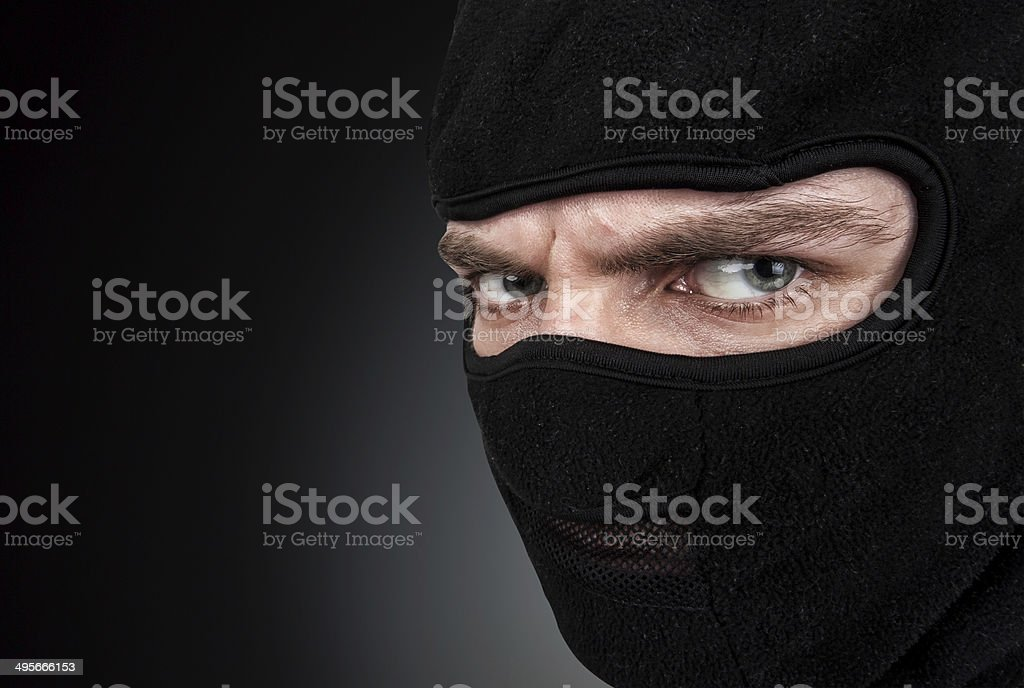 Man in a mask on black background stock photo