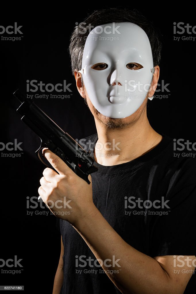 Man in a Mask with a Gun stock photo