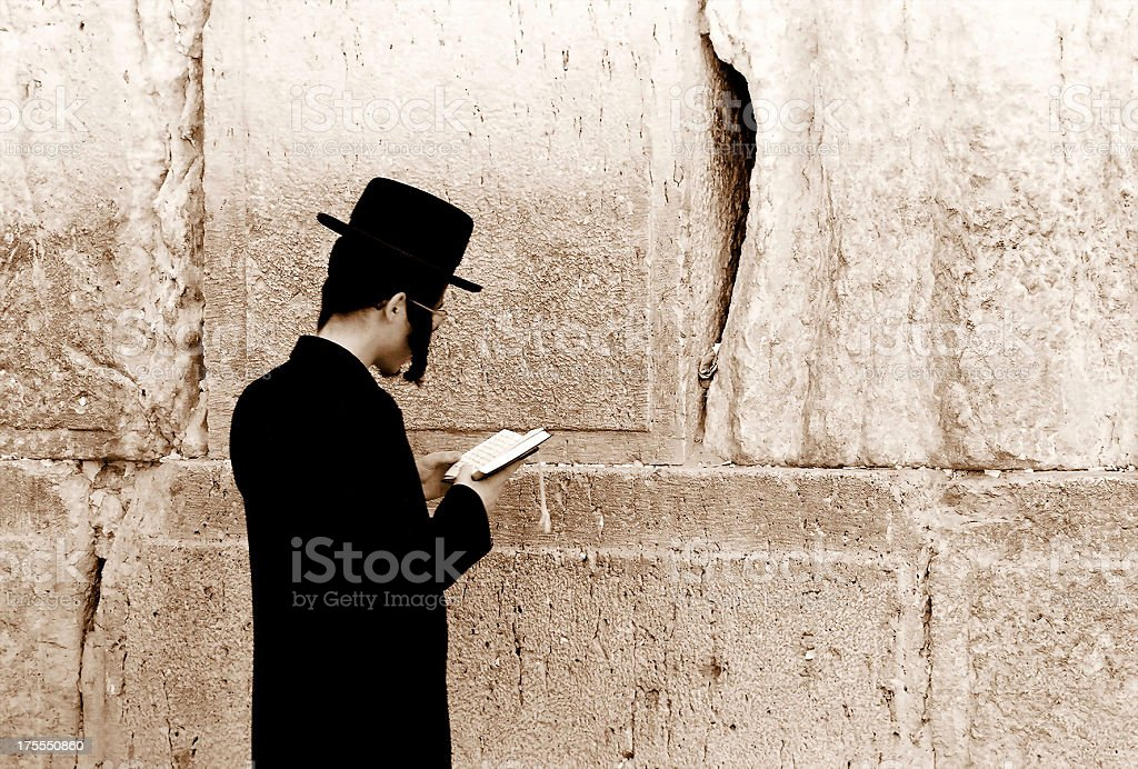 Man in a retro hat reading a book in front of a wall royalty-free stock photo