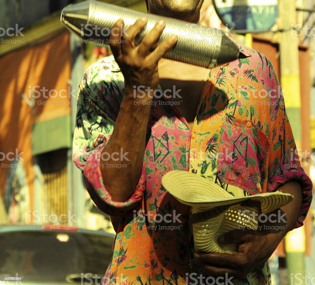 Man in a samba shirt shaking a percussion instrument royalty-free stock photo