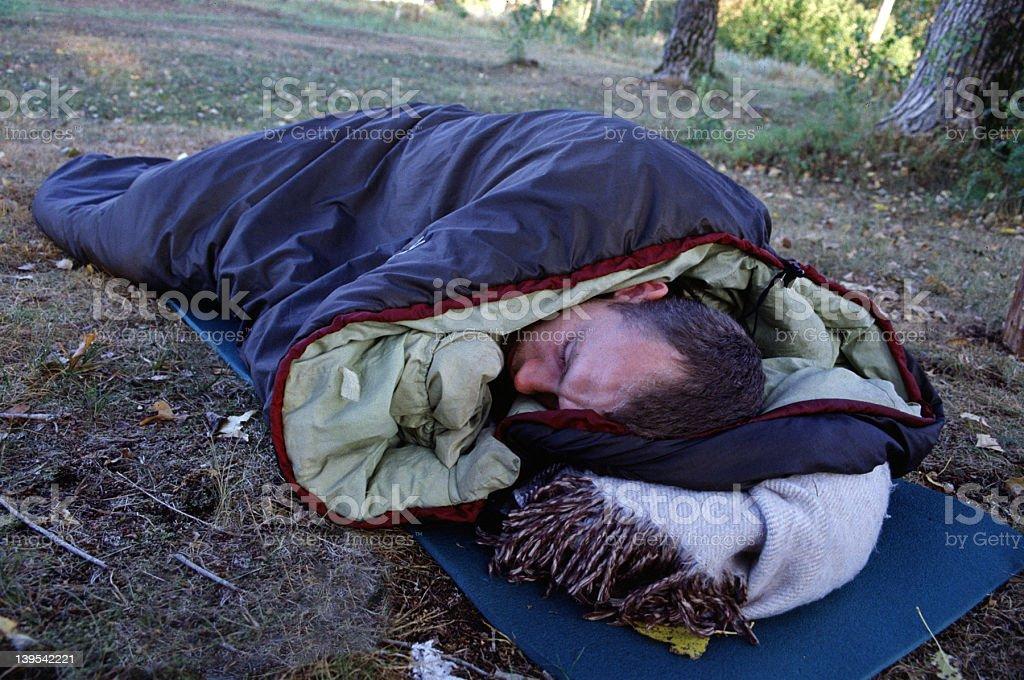 Man in a sleeping bag stock photo