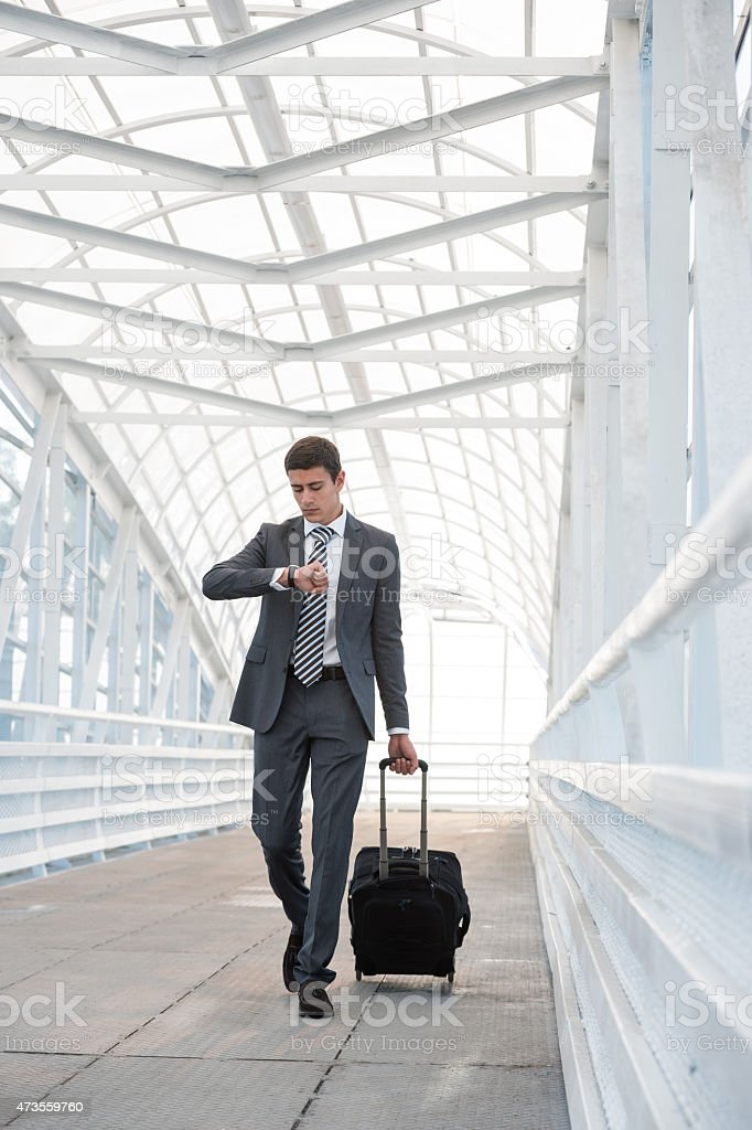 A man in a suit at an airport carrying his suitcase stock photo