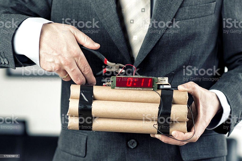Man in a suit defuse bomb with wire cutter stock photo