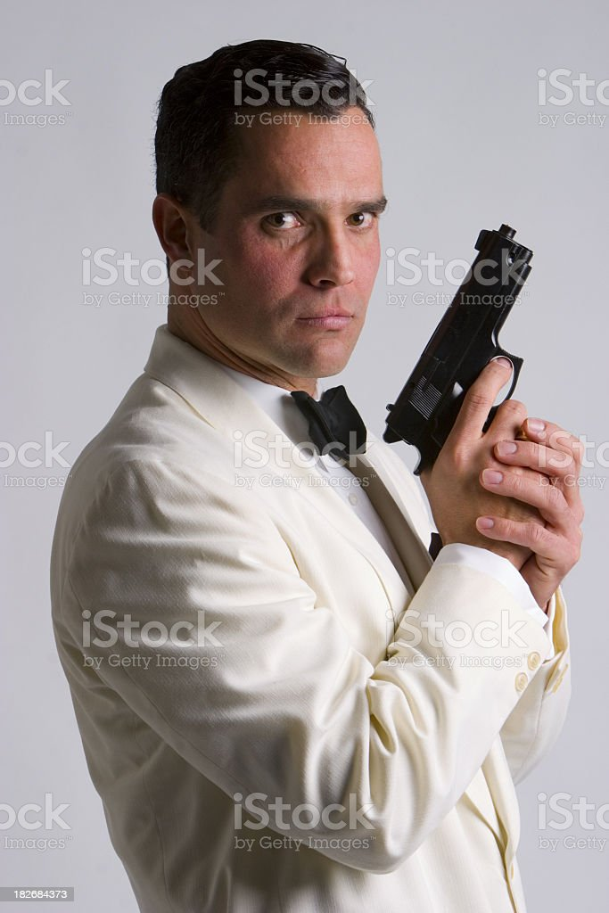 A man in a suit holding a gun like a spy stock photo