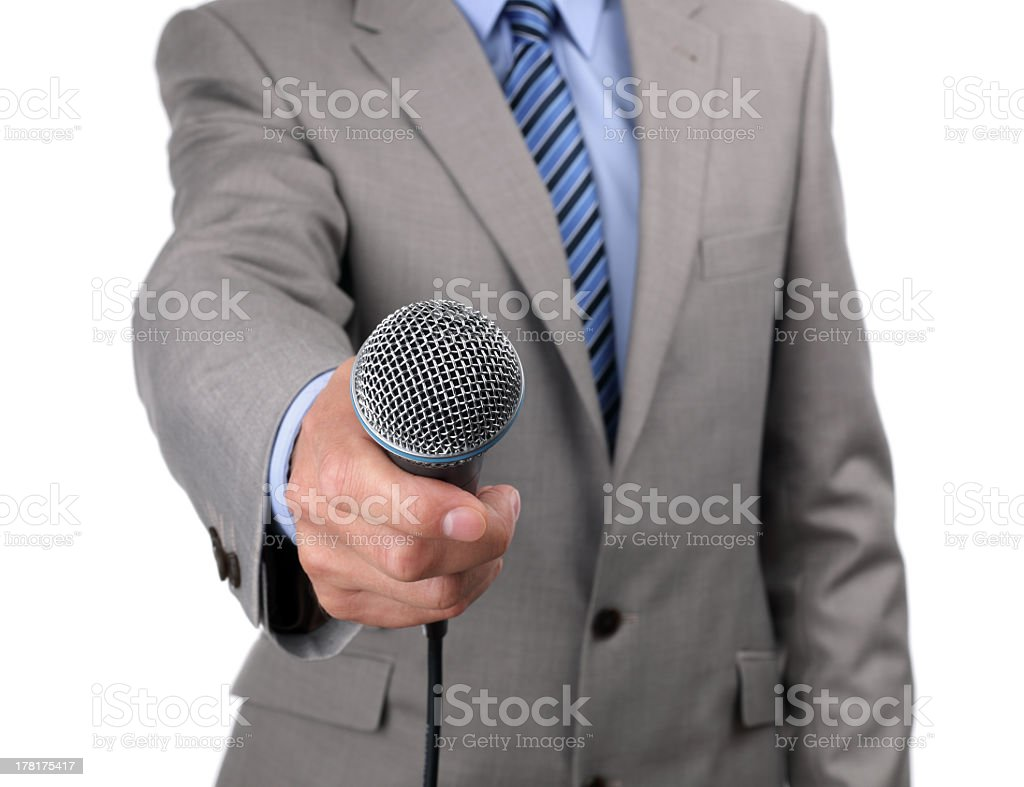 Man in a suit holding a microphone towards the camera stock photo