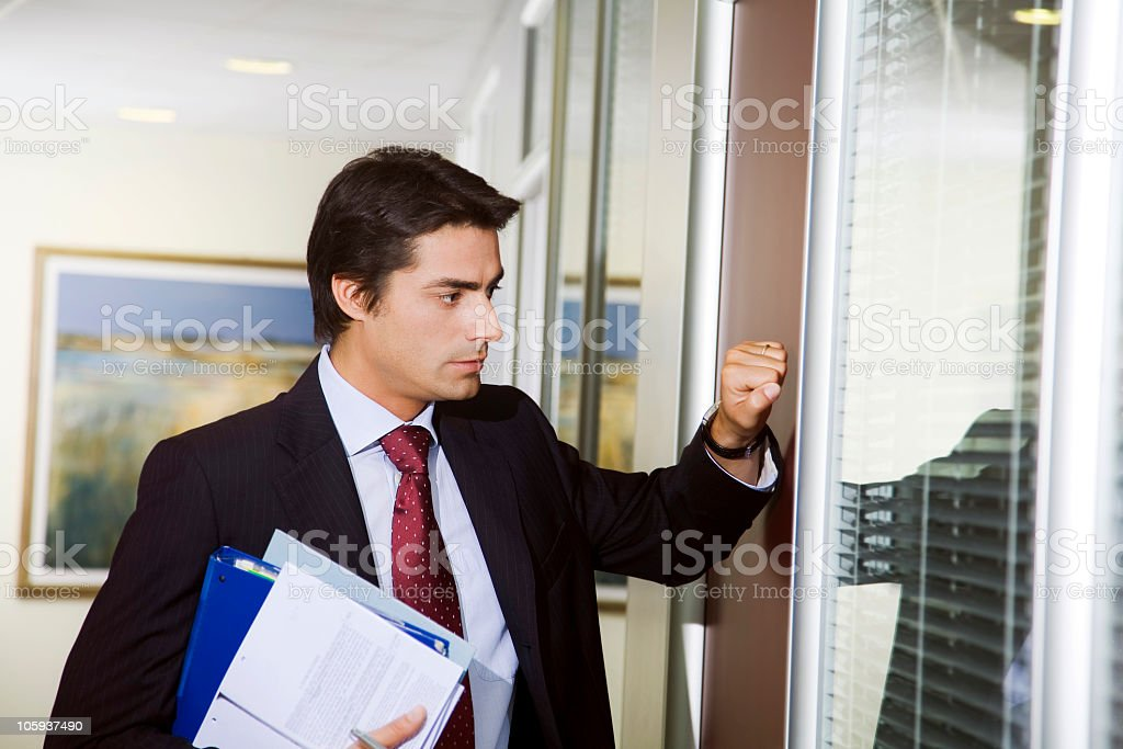 A man in a suit in an office knocking on the door stock photo