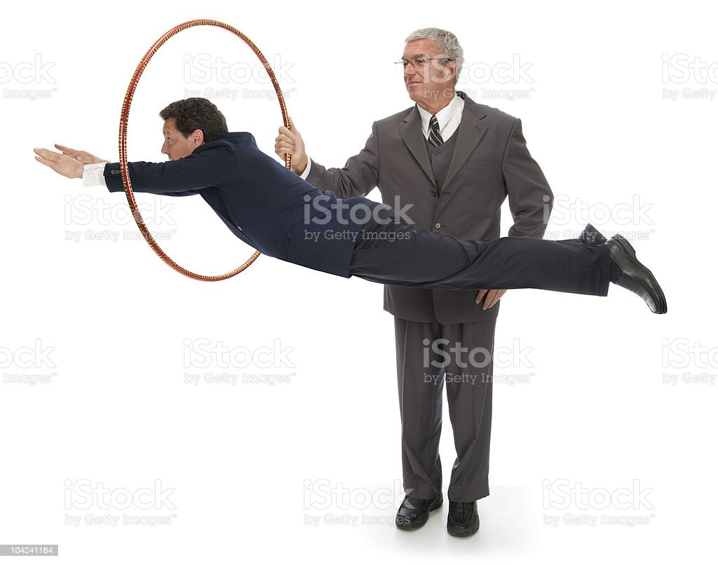 Man in a suit jumping through hoops stock photo