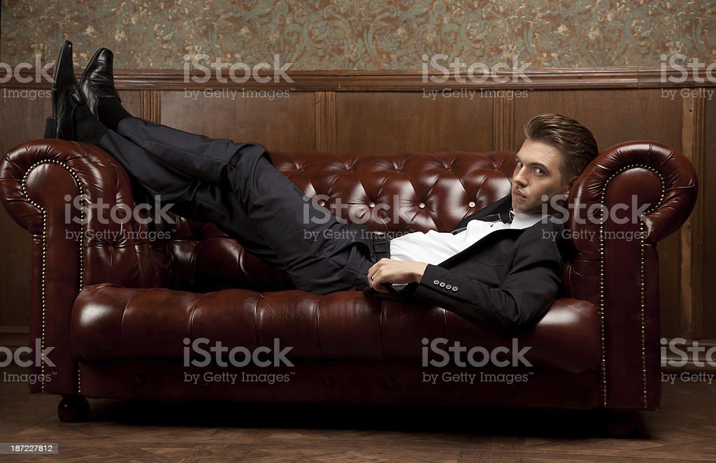man in a suit lying on the couch royalty-free stock photo