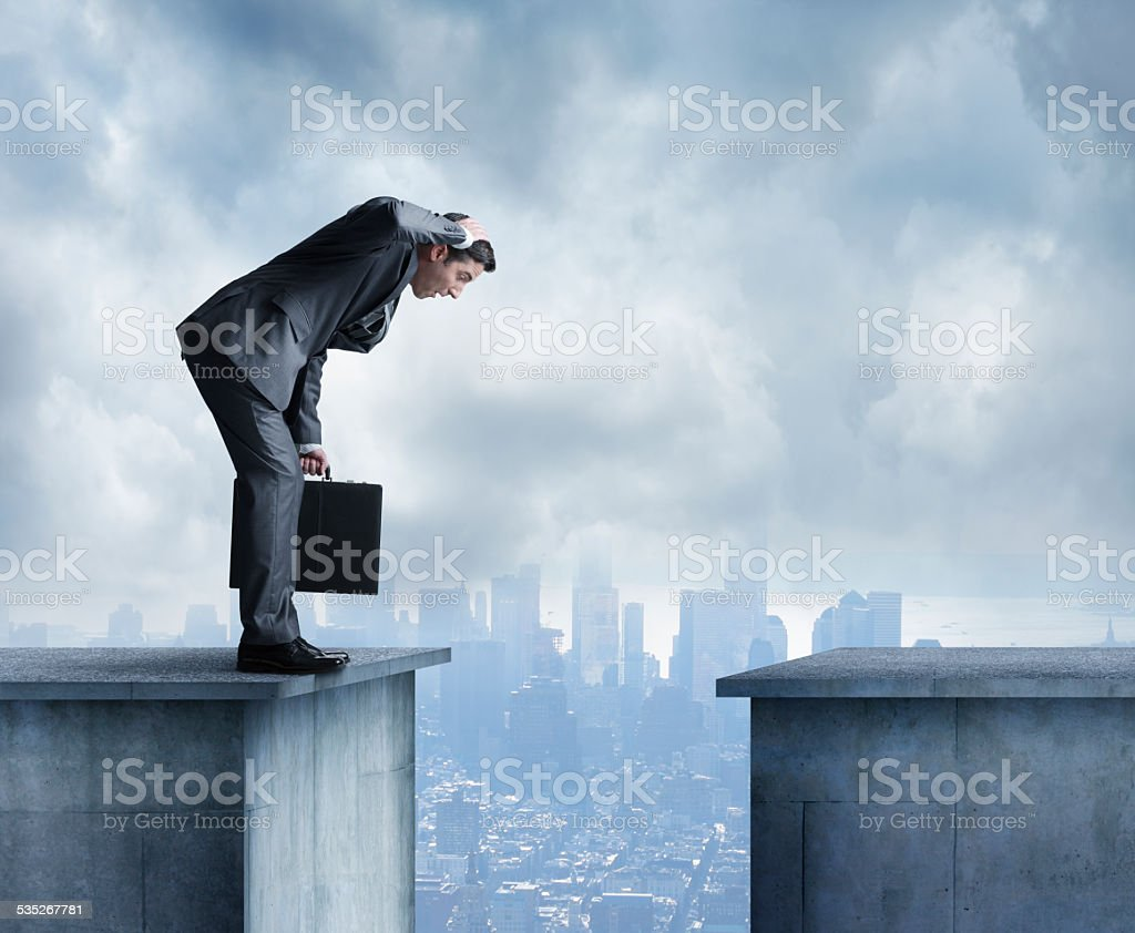 Man in a suit stares at space between two buildings stock photo