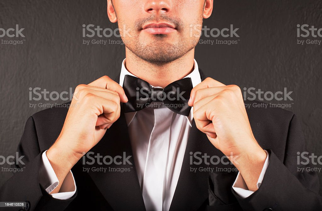 A man in a suit tying his bow tie stock photo
