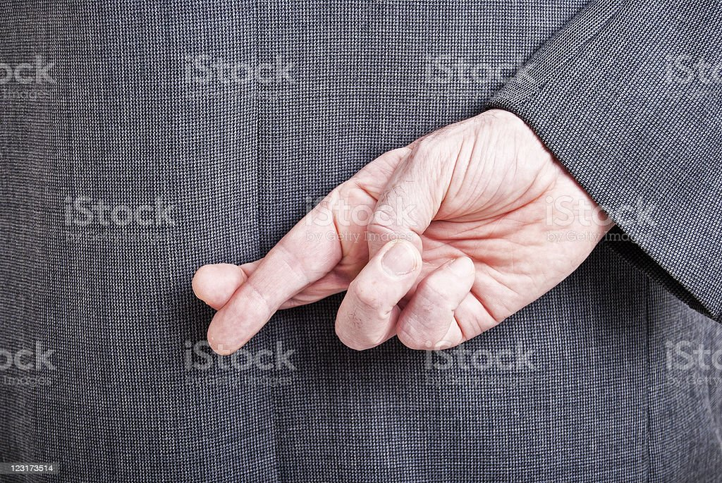 Man in a suit with his fingers crossed behind his back stock photo