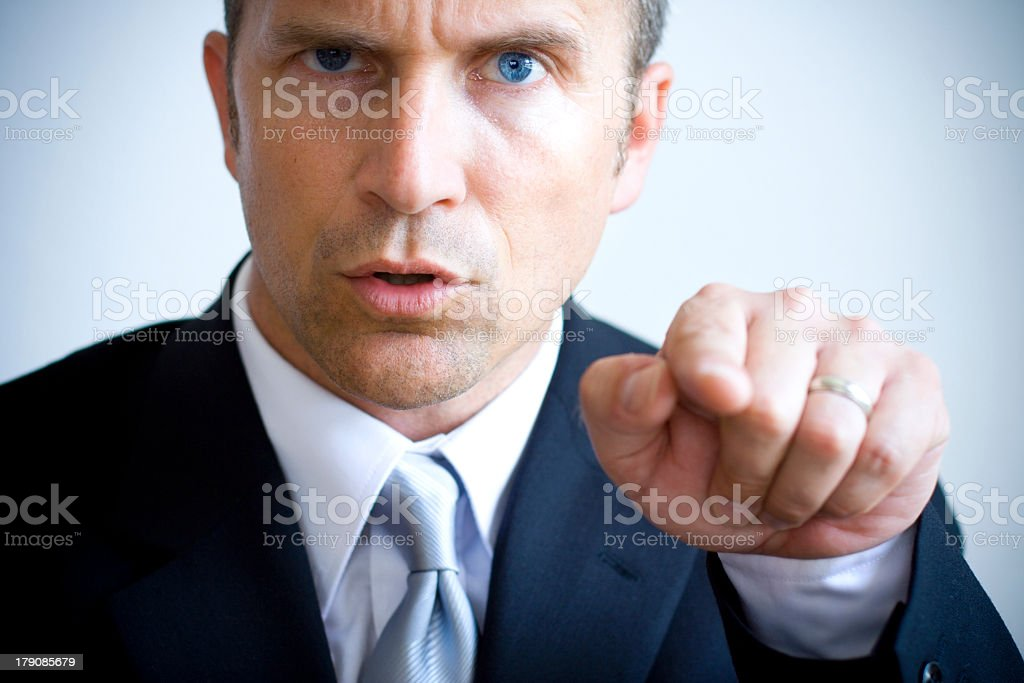 A man in a suit with piercing blue eyes pointing his finger stock photo