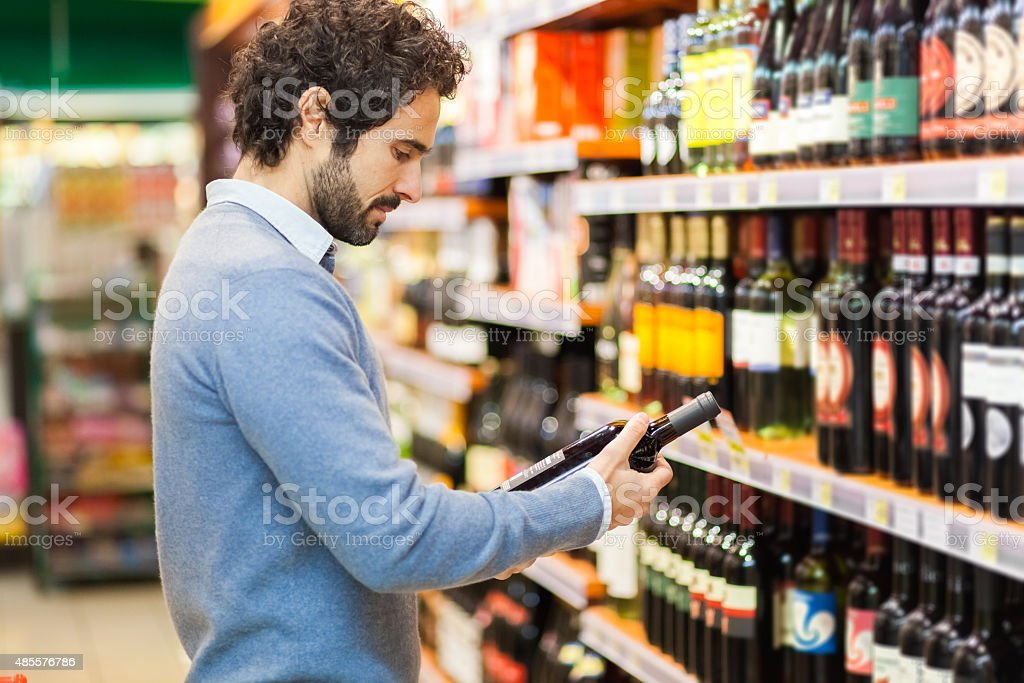 Man in a supermarket choosing wine bottle stock photo