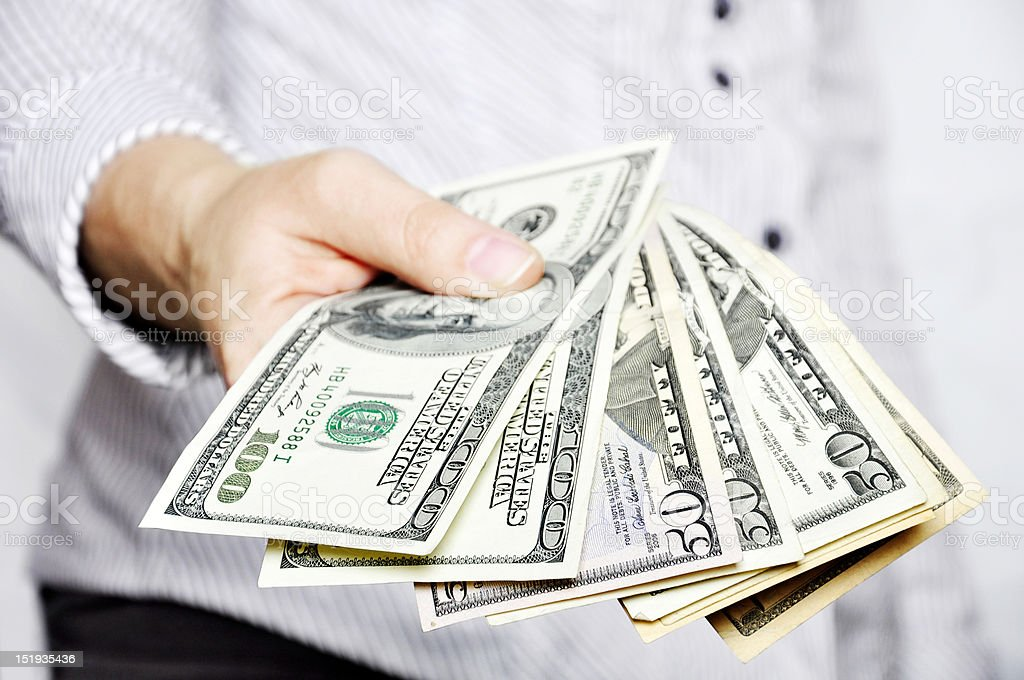 Man in a sweater holding a stack of money stock photo