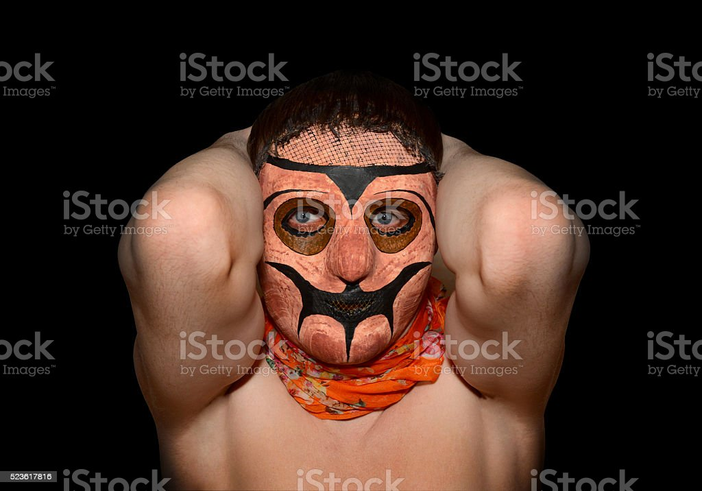 Man in a terrible mask with hands behind head stock photo