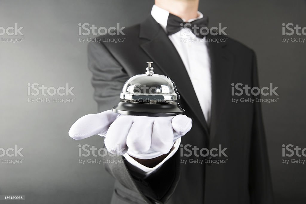 A man in a tuxedo and gloves holding a bell stock photo
