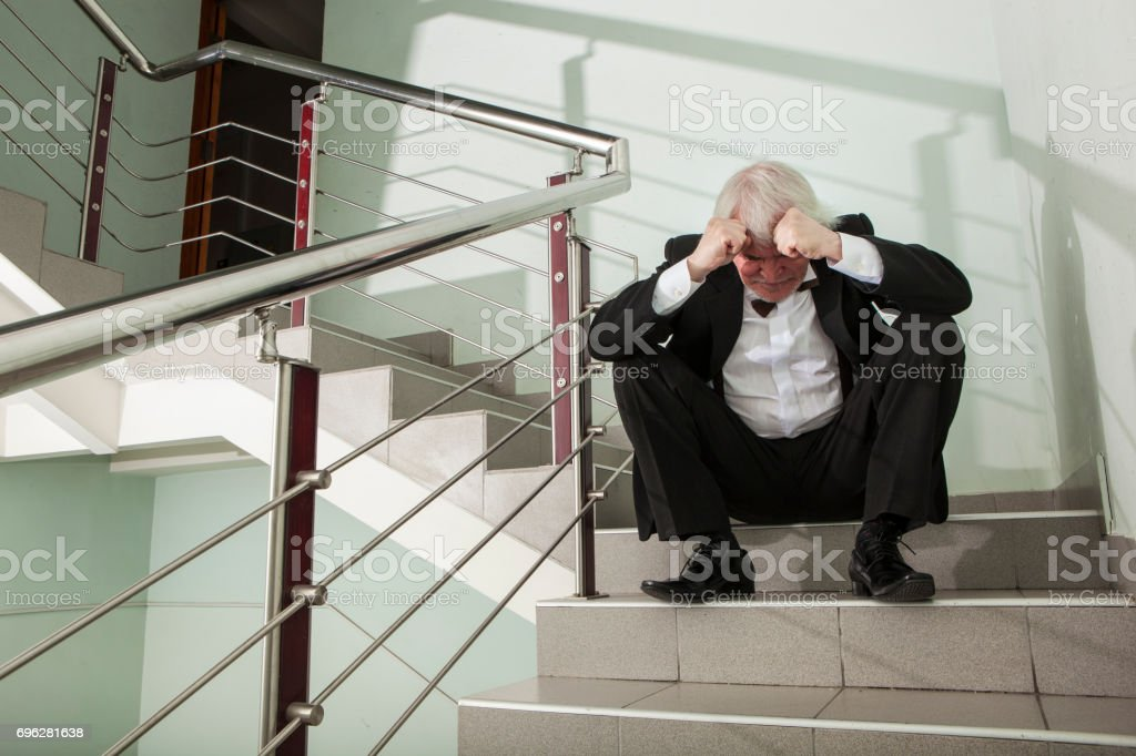 Man in a tuxedo on a metal ladder stock photo