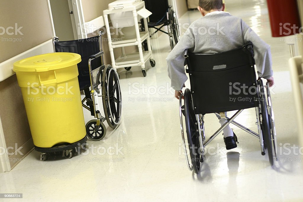 A man in a wheel chair in motion in the hospital stock photo