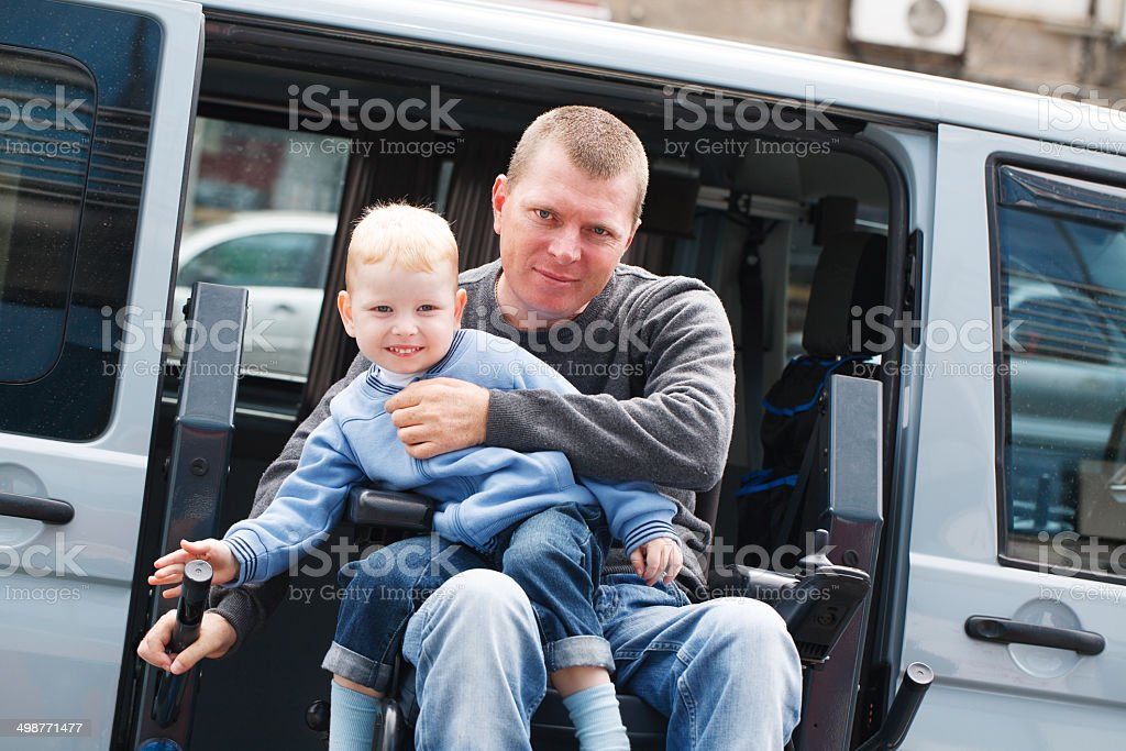 A man in a wheelchair holding a young child stock photo