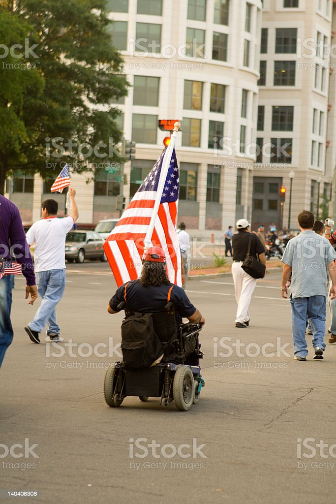Man in a Wheelchair Holding American Flag During Protest royalty-free stock photo