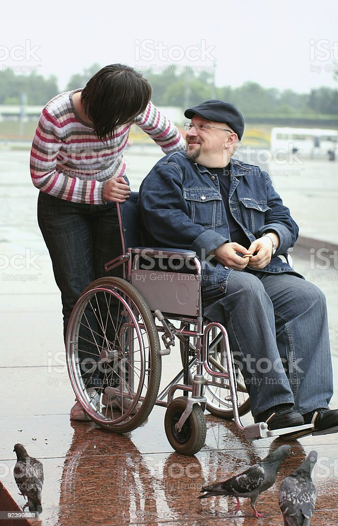 Man in a wheelchair talking with woman royalty-free stock photo