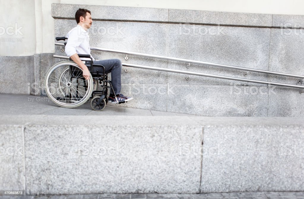 Man in a wheelchair using accessible ramp stock photo
