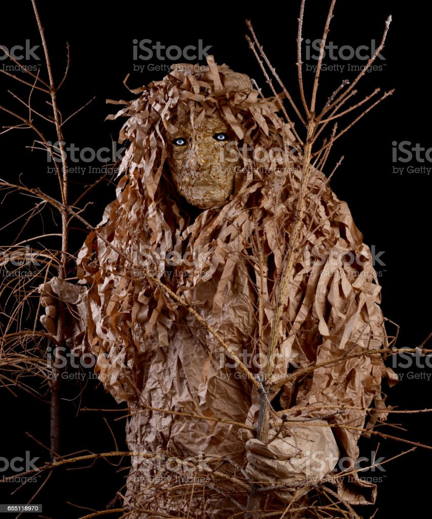 Man in a wood goblin costume, holding a withered trees stock photo