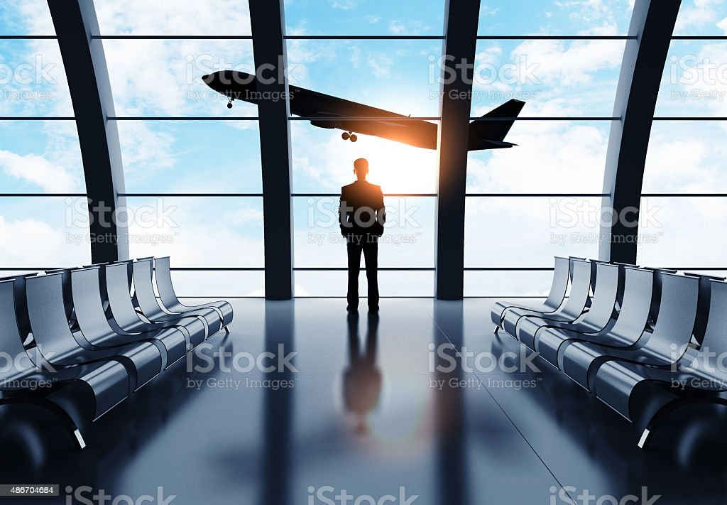 man in airport looking on airplane stock photo