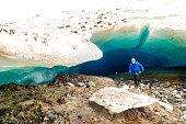 Man in Alaskan blue-green glacier ice cave