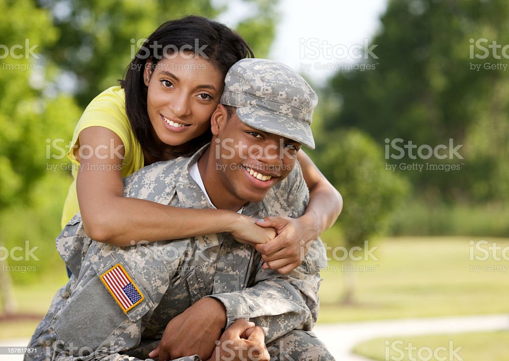 Man in American military uniform being embraced by woman royalty-free stock photo
