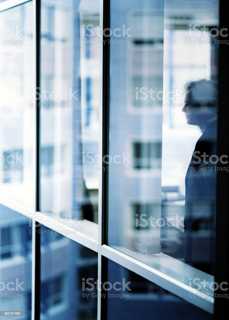 man in an office looking out of the glass royalty-free stock photo