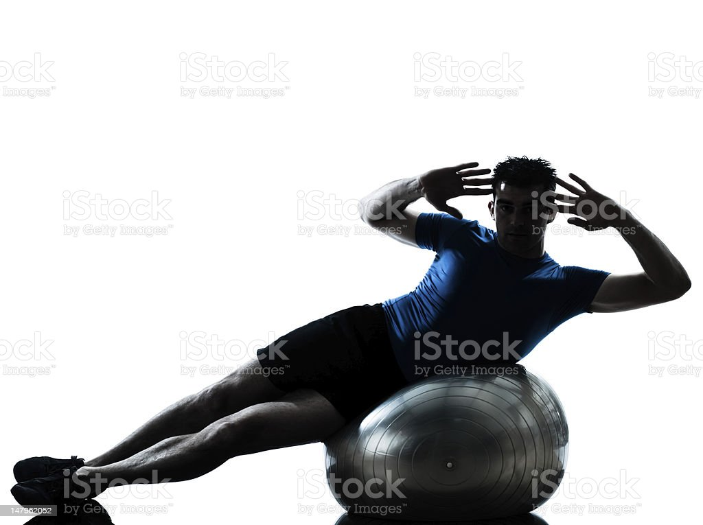Man in athletic clothes exercising with fitness ball royalty-free stock photo
