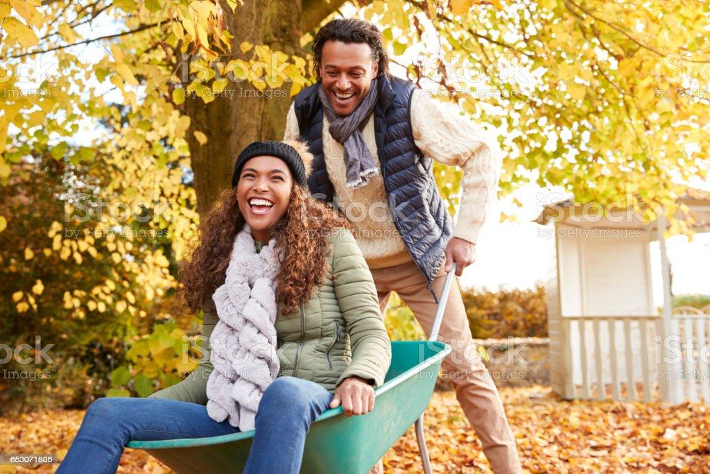 Man In Autumn Garden Gives Woman Ride In Wheelbarrow stock photo