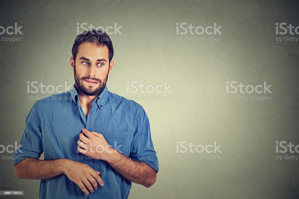 man in awkward situation, playing nervously with hands stock photo